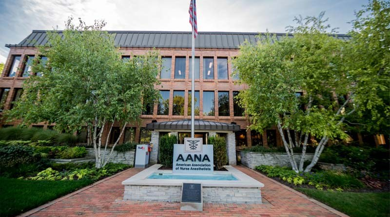 Brown building with a water fountain and American flag in front of it.