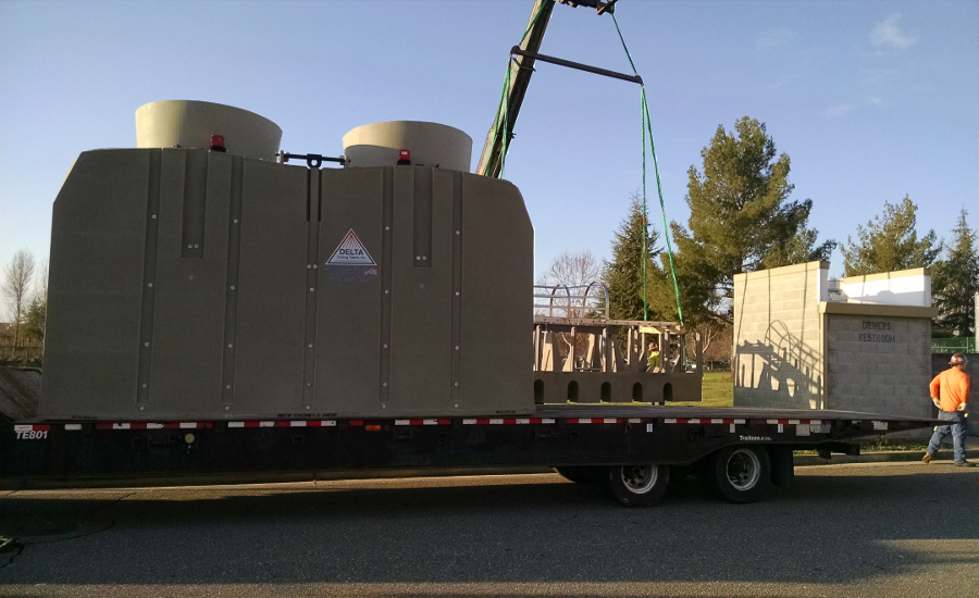 Delta Cooling Towers Beige Twin TM Series on a flatbed of a truck waiting to drive off.  Under the flatbed you can see the black pavement and above it is blue skies. A construction worker is seen in the right side of the image wearing an orange top, jeans and a hard hat.