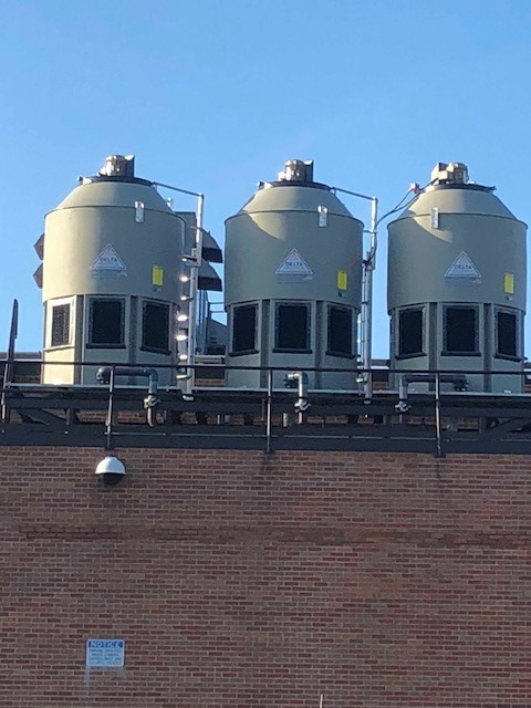 Three beige Delta Paragon cooling towers resting on top of a red brick building with the blue sky behind them.