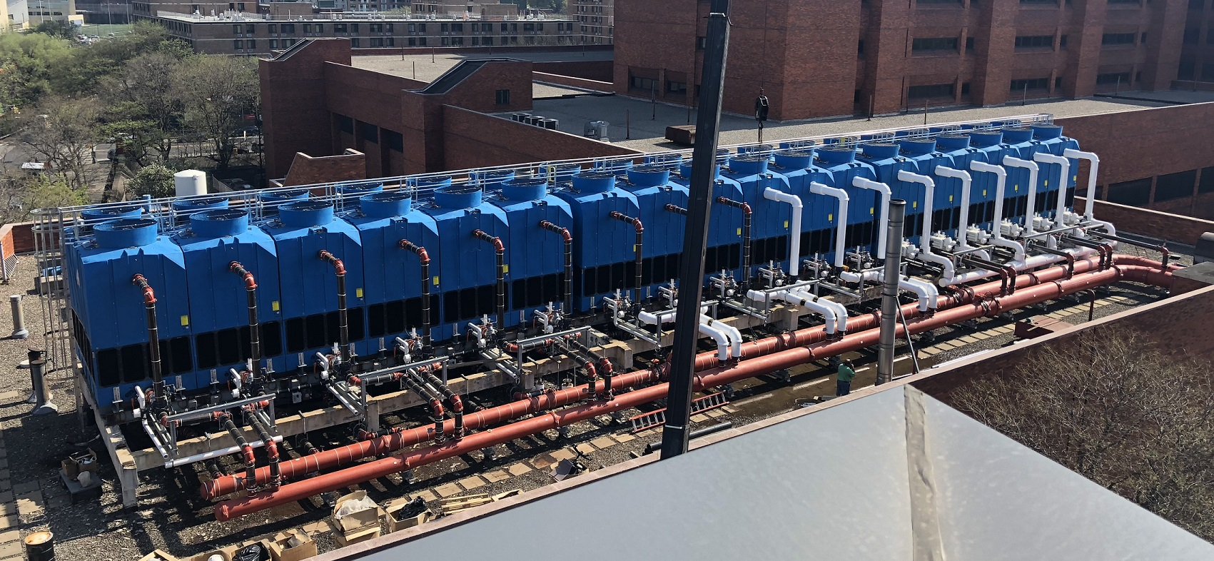 ighteen TM Series Anti-Microbial Cooling Towers lined up in a row on the roof of a hospital in NY. Buildings are in the background.