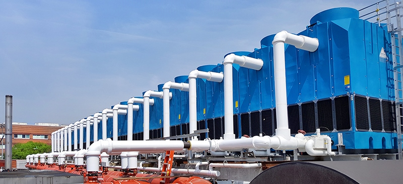 Multiple Blue Delta Anti-Microbial Cooling Towers taken on an angle to see the towers in the distance. White piping comes out of the towers and moves into the building.