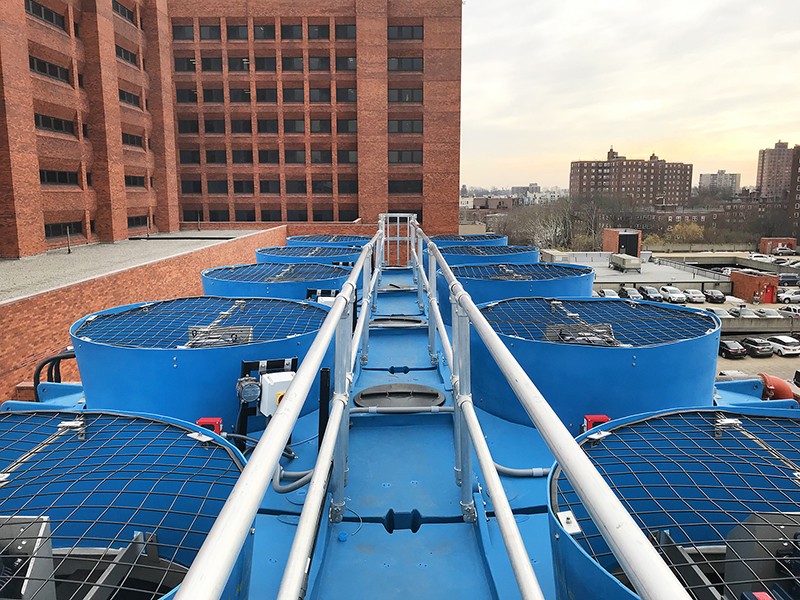 Roof view of Delta Cooling Towers Anti Microbial Towers on top of Lincoln Hospital in New York. You can see the New York skyline in the background with brick buildings. Only the top of the cooling towers are in view.
