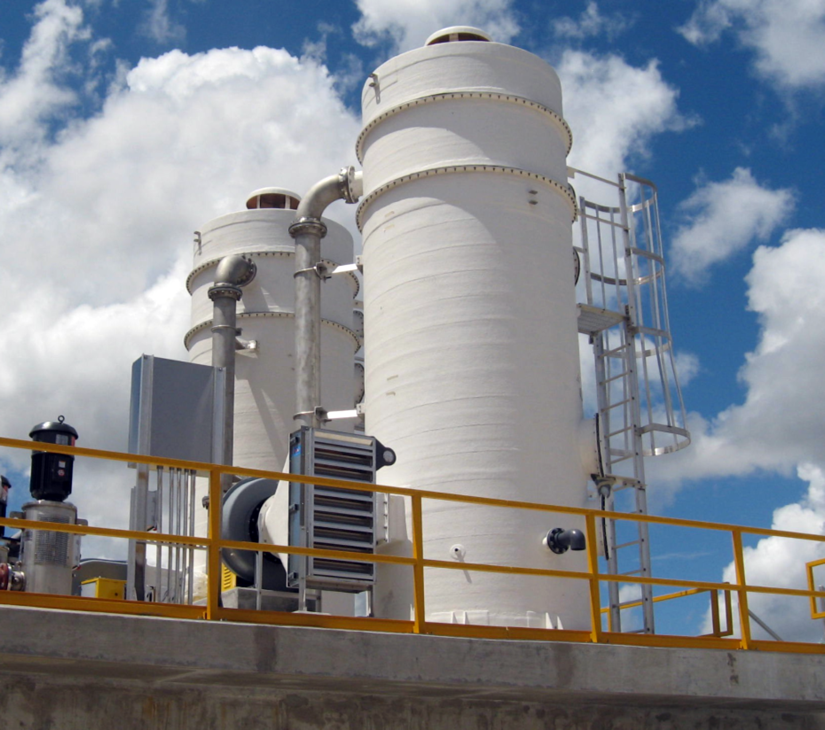 """Delta Cooling Towers, Inc. designed and fabricated Two 7'-0"""" Diameter x 20'-0"""" high air stripping towers to treat potable water at the Hollywood Seminole Water Treatment Plant in Florida. The two white towers are surrounded by a protective yellow gate. In the background there is blue skies with white puffy clouds."""