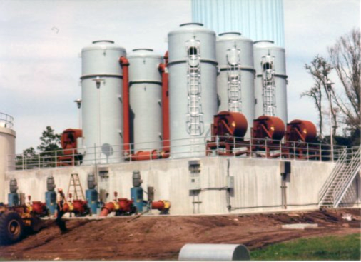 """Delta Cooling Towers, Inc. was contracted by the City of Orlando, Florida to design and fabricate six 9'-0"""" Diameter x 21'-0"""" high air stripping towers to treat potable water at the Econlackhatee Water Treatment Facility.  The six towers are close together on a concrete structure. There are red pipes coming down from the air strippers. The structure is surrounded by dirt and grass with a light blue sky in the background with some trees."""