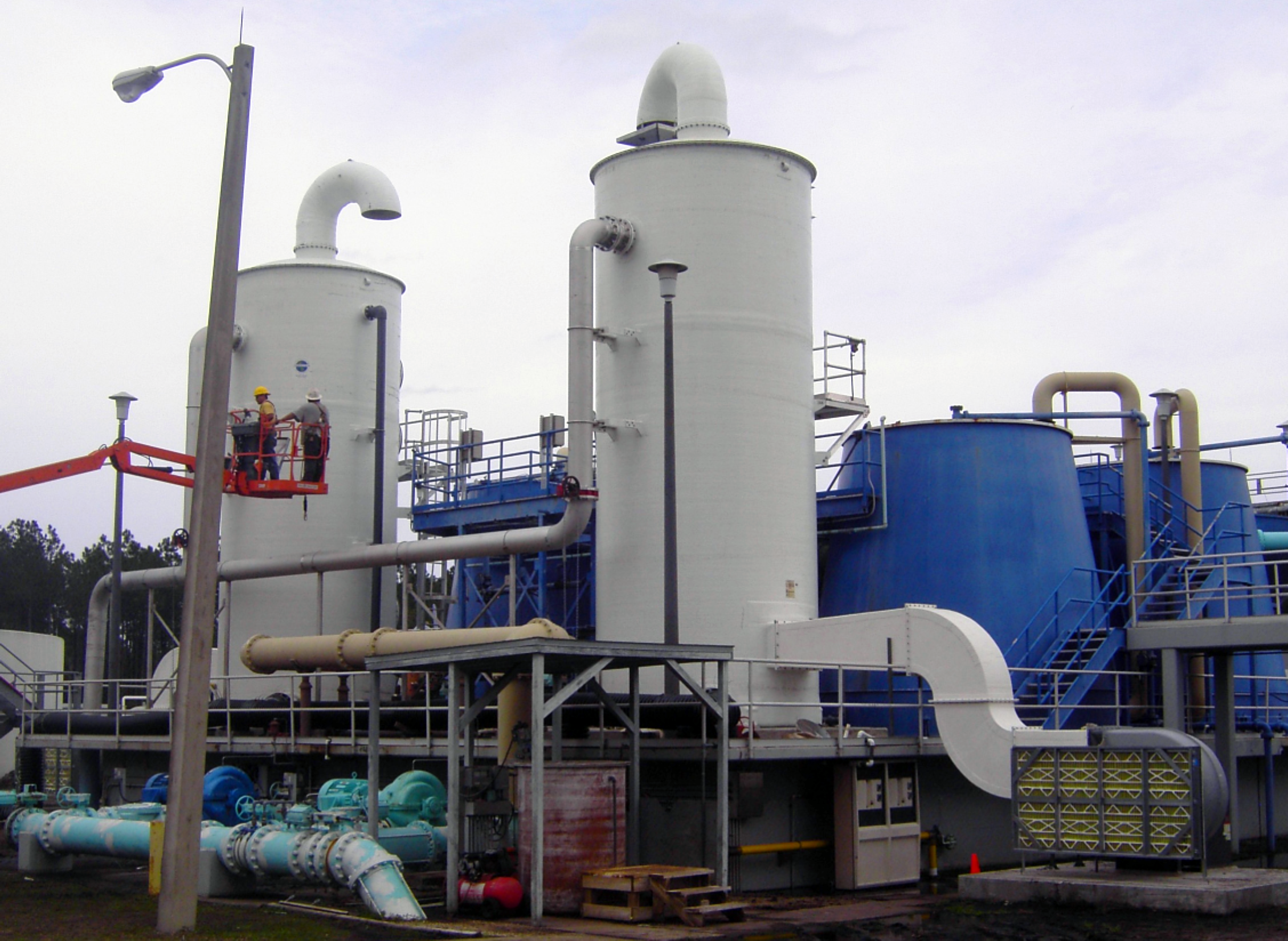 """Two 11'-0"""" Diameter x 37'-2"""" high Delta air stripping towers to treat potable water at the Water Treatment Plant site in St. Augustine, Florida. The two white towers are connected to additional systems. Two men are on a platform next to the air strippers."""