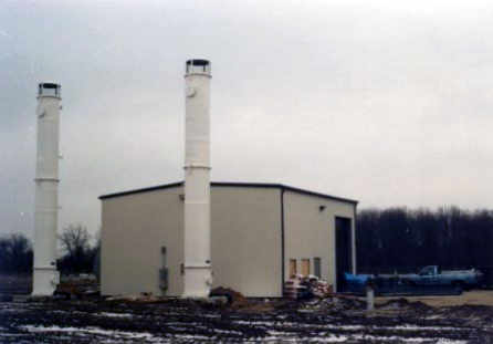 "Delta designed, fabricated, and delivered (2) two 4'-0"" Diameter x 35'-0"" high air stripping towers to treat the contaminated water with each tower containing Delta Pak structured packing. The photo looks old with gray skies and trees in the back. The two towers are next to a beige building with brown mud around it."