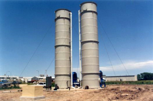 "Delta Cooling Towers, Inc. designed and fabricated (2) two 4'-0"" Diameter x 40'-0"" high air stripping towers to treat water at the Water Treatment Plant in Clinton, Iowa. The two white towers are indoor with red pipes. There is a yellow connecting the two with one tower having a ladder on the side of one."