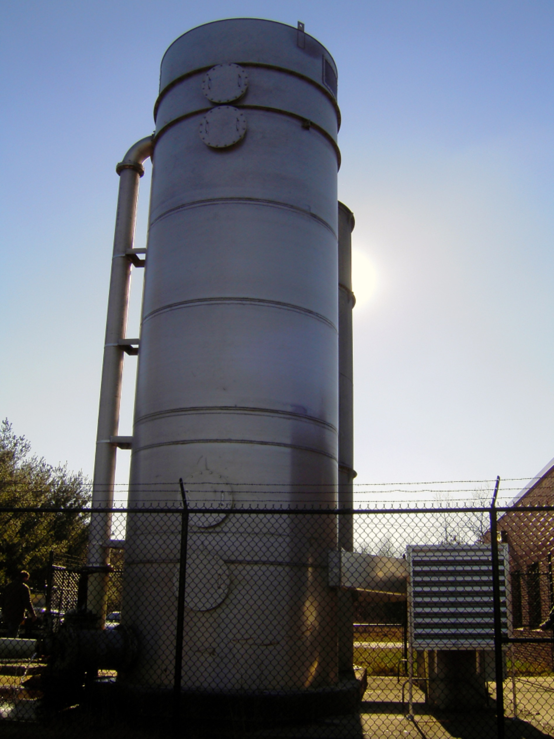 "One 10'-0"" Diameter x 30'-6"" high Silver Stainless Steel Delta Cooling air stripping tower to treat potable water at the Water Treatment Facility.  The tower is surrounded by a metal fence, next to a building with some trees to the side. The background has blue skies with no clouds."