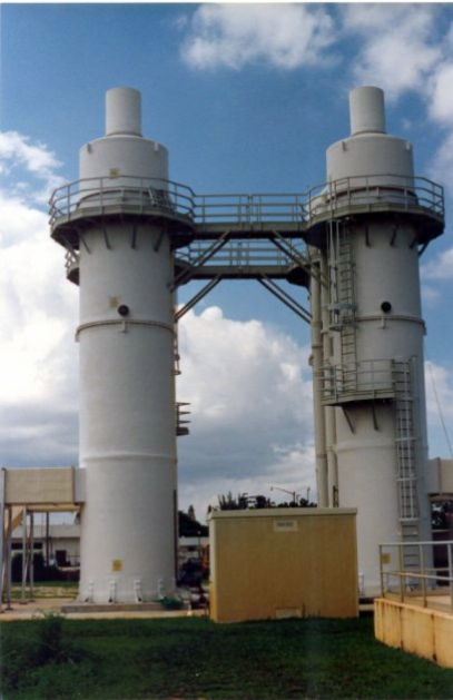 "Four 10'-0"" Diameter x 34'-0"" high air stripping towers were designed and fabricated by Delta Cooling Towers, Inc. to treat potable water at the Water Treatment Plant in Delray Beach, Florida. There is a bridge connecting  the four towers with a yellow box in front with green grass and blue skies with white clouds."