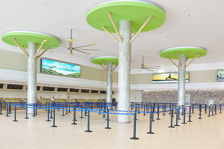 Punta Cana Airport installed a Delta Cooling energy efficient cooling tower system. There are big columns that are beige with a circular green top that makes them look like trees. There are poles that have lanes marked out with blue posts.